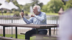 4K Senior man relaxing in the park & making video call with smartphone Stock Footage