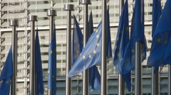 EU European Union flags wave Brussels Commission building sunny close up detail Stock Footage