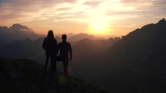 Aerial, edited - Raising above couple watching beautiful sunset in the mountains Stock Footage
