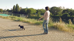 Young woman going along path with little funny dog Stock Footage
