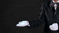 4K Tuxedo Man Gestures, Open Hand Reveal to Center Screen, Dark Grey Background Stock Footage