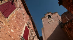 Ochre colored facades in Rousillon village, Provence, France, pan Stock Footage