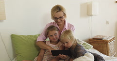 Happy grandmother with kids playing games on tablet at home Stock Footage