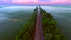 Flying over surreal foggy landscape with railroad tracks at daybreak Stock Footage