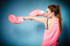 Female boxer wearing big fun pink gloves playing sports - stock photo