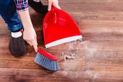 Cleaning woman sweeping wooden floor - stock photo