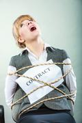 Afraid woman bound by contract tied to chair. Stock Photos