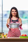 Female cook preparing soup in brightly lit kitchen Stock Photos