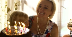Senior woman blowing out the candles, her little granddaughter helping her. They - stock footage