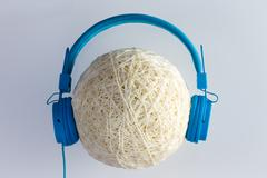 Single ball of waxed string with blue headphones Stock Photos