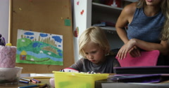 Smiling mom watching at her child drawing at table in nursery Stock Footage