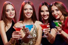 Row of girls with toothy smiles cheering up with cocktails Stock Photos