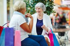 Two friendly pensioners with shopping bags talking in trade center Stock Photos