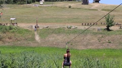 Girl sliding down a zip line between hills in village Pirogovo, Kiev, Ukraine Stock Footage