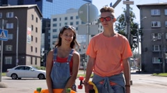Teenage couple with penny boards walking in city Stock Footage