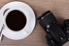 Coffee cup and camera on a wooden surface Stock Photos