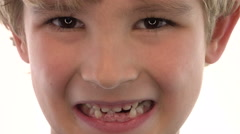 Little boy with missing teeth grinning at camera on white background Stock Footage