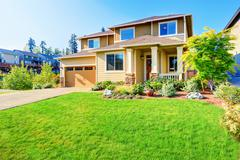 Beautiful curb appeal of luxury beige house with well kept front garden. Nort Stock Photos