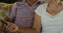 Loving caring senior couple relaxing at home sitting on sofa watching TV. Mature Stock Footage