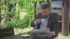 Businessman reading newspaper drinks coffee, steadicam Arkistovideo