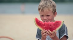 Litttle boy eating delicious watermelon on beach Stock Footage