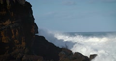 Large waves roll into the coast of Hawaii in slow motion and break along a Stock Footage