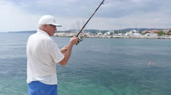 Senior man fisherman chase fish with fishing rod on a pier of Halkidiki Greece Stock Footage