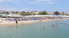 Greece Halkidiki Aegean Sea resort beach - people rest swim and take sunbathes Stock Footage