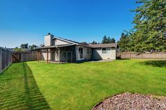 Fenced Backyard garden with cage and green grass.  American Rambler house ext Stock Photos