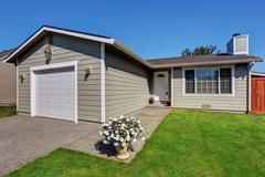 Exterior of American one level rambler house with white garage door and flowe Stock Photos