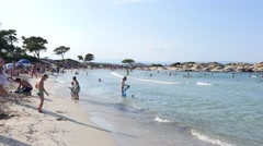 Greece Halkidiki sand beach resort on Aegean Sea - people rest and children play Stock Footage