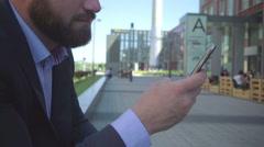 Businessman browsing smartphone. Close and tilt shot, steadicam. Stock Footage