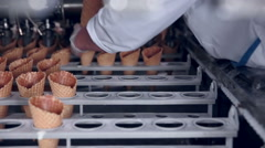 Close-up shot of a moving belt with ice-cream cones and a worker taking them - stock footage