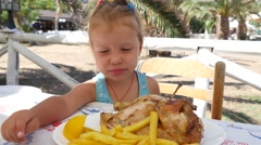 Little girl child eat french fries and bite chew chicken meat dish kid food diet Stock Footage