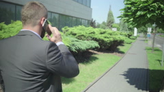 Businessman talking by smarphone, going to work, steadicam Stock Footage