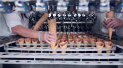 Close-up shot of a moving belt with ice-cream cones and a worker taking them Stock Footage