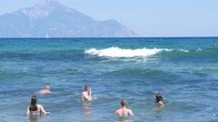 Greece Halkidiki sea resort beach people swim big waves background Mount Athos Stock Footage