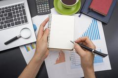 Closeup of a young woman checking accounts. Office desk table with supplies top Stock Photos
