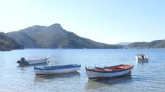 Fishing boats are tied up at the shore of picturesque bay in Aegean Sea Greece Stock Footage