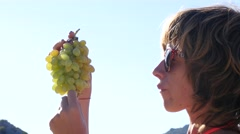 Young woman on sea resort eating grape fruits at sky background portrait closeup Stock Footage
