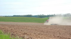 An agricultural tractor plowing a field. Hills and a forest at the background Stock Footage