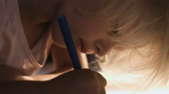 Calm little girl drawing lying on the floor in the sunny living-room, close-up Stock Footage