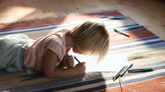 Cute little girl on the floor thinking on a drawing concept - stock footage