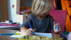 A child with long blond hair is painting something with markers pens, looking Stock Footage