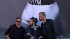 Trendy guys next to a poster advertising men's underwear. Slow Motion. Stock Footage