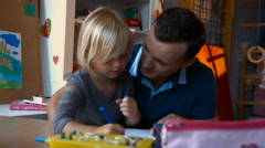 Young father and son drawing with colored pencils on the nursery table Stock Footage