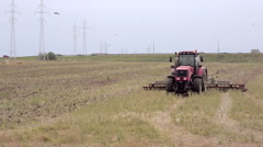 An agricultural tractor, plowing a field for sowing, moving to the camera. Birds Stock Footage