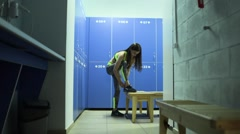 Young woman tying up sneakers in fitness club locker room Stock Footage