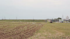 A side and back view of an agricultural tractor, plowing a field for sowing Stock Footage