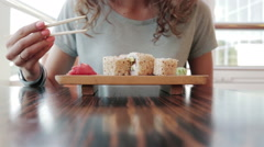 Young woman in cafe eating sushi with chopsticks Stock Footage